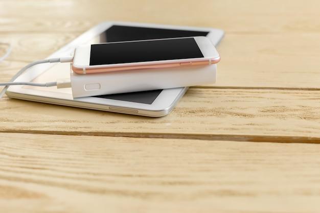 Powerbank und mobiltelefon auf holztisch