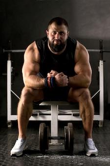 Powerlifter mit starken armen bereitet ein gewichtheben vor. muskulöser mann, der im fitnessstudio trainiert. gesundes lebensstilkonzept.