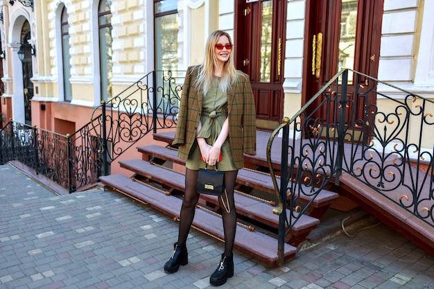 Prächtige blonde stilvolle frau posiert auf der straße in der nähe von luxus-hotel im klassischen stil, europäische atmosphäre, modernes trendiges outfit, blogger posiert auf der straße.