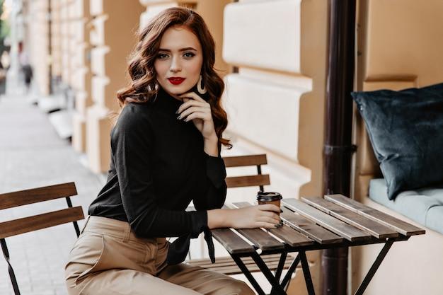 Prächtige junge dame, die am holztisch auf der straße sitzt. anmutiges ingwermädchen, das kaffee im freien genießt.
