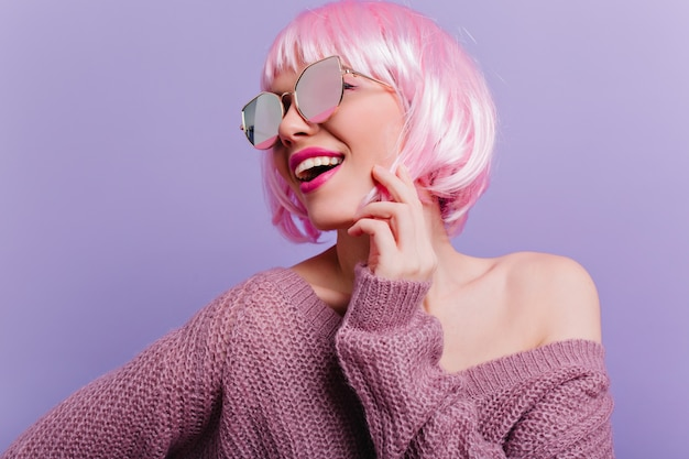 Prächtige junge dame in der rosa perücke, die mit vergnügen innen-nahaufnahmefoto des hübschen trendigen mädchens in der perücke lokalisiert auf lila wand aufwirft.