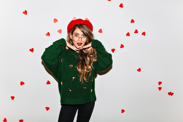Prächtiges weibliches modell im grünen pullover, das überraschte gefühle ausdrückt
