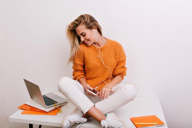 Prächtiges weibliches modell im trendigen pullover, der an ihrem arbeitsplatz mit gekreuzten beinen sitzt und telefon hält