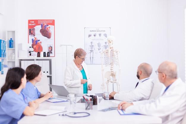 Präsentation über die menschliche anatomie mit skelett während der medizinischen konferenz. klinikexperte, der mit kollegen über krankheiten spricht, mediziner.