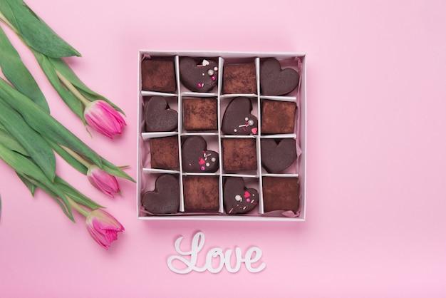 Präsentieren sie box mit schokoladenbonbonsherzen und tulpen auf rosa hintergrund. wüste zum valentinstag