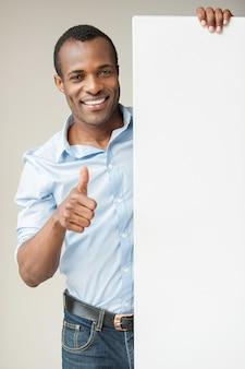 Präsentieren sie ihr produkt. fröhlicher afrikanischer mann im blauen hemd, der sich an den kopierraum lehnt und seinen daumen nach oben zeigt, während er vor grauem hintergrund steht