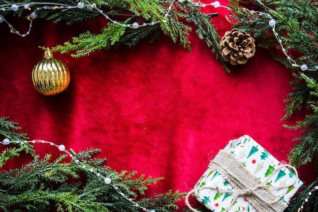 Präsentkarton in der nähe von weihnachtskugel und baumstumpf zwischen nadelbäumen