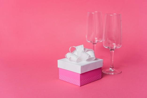 Präsentkarton mit leere champagnerglasgläser auf rosa hintergrund