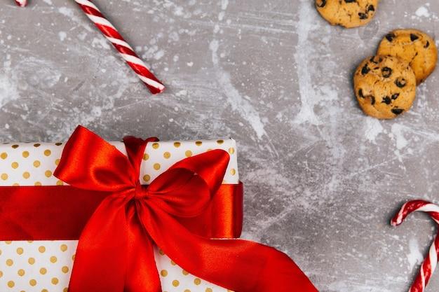 Präsentkarton mit rotem band liegt auf grauem boden mit weihnachtsplätzchen, lebkuchen und roten weißen süßigkeiten