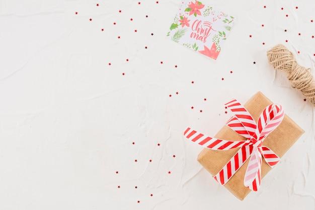 Präsentkarton zwischen konfetti, fäden und postkarte