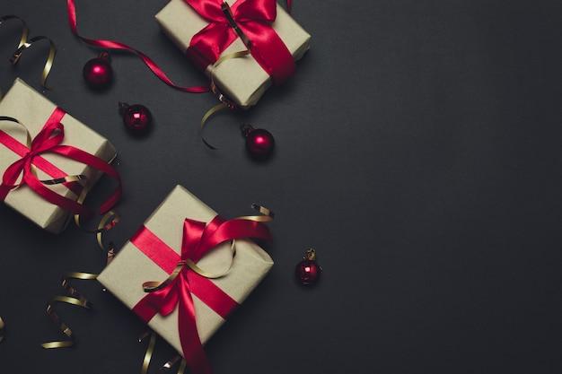 Präsentkartons auf hintergrundfeiertags-grußkartenkonzept des dunklen schwarzen.