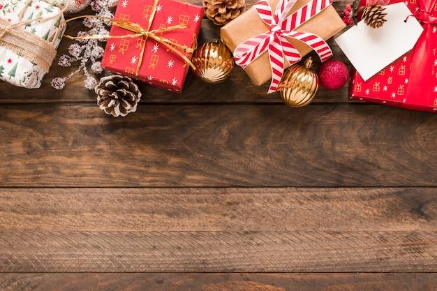 Präsentkartons in weihnachten verpackt mit bändern in der nähe von ornamentkugeln