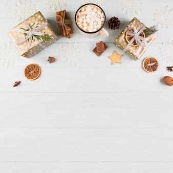 Präsentkartons in weihnachtsverpackung in der nähe von cup mit marshmallows