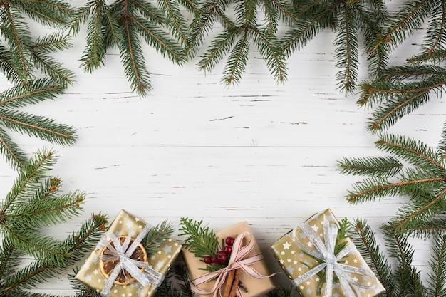 Präsentkartons in weihnachtsverpackung in der nähe von tannenzweigen