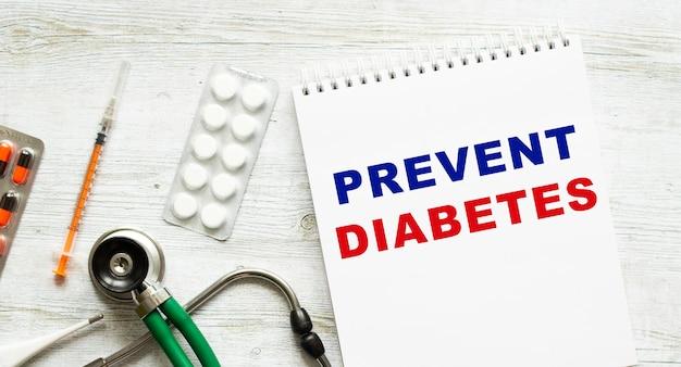 Prävent diabetes steht in einem notizbuch auf einem weißen tisch neben pillen und einem stethoskop. medizinisches konzept