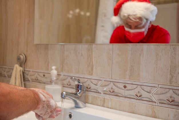 Prävention der coronavirus-pandemie. mann wäscht sich zu hause die hände mit einer chirurgischen maske wegen coronavirus, mit einer weihnachtsmütze auf dem kopf. fokus auf schaum