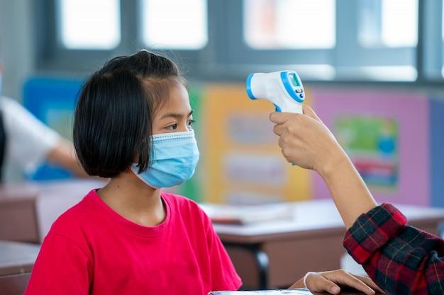 Prävention gegen covid-19 im klassenzimmer der grundschule, schutz gegen covid-19 und coronavirus-infektion.