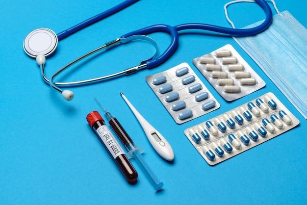 Prävention und behandlung des coronavirus-gesundheitskonzepts - spritze, maske, tabletten, stethoskop und