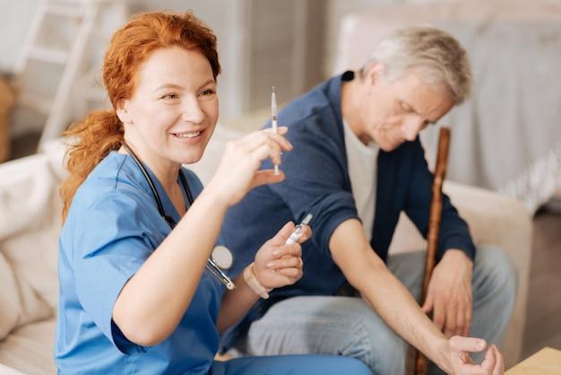 Präzises verfahren. qualifizierter ausgebildeter medizinischer mitarbeiter, der eine sterile spritze zum injizieren einiger vitamine verwendet, die zur stärkung des immunsystems des patienten benötigt werden