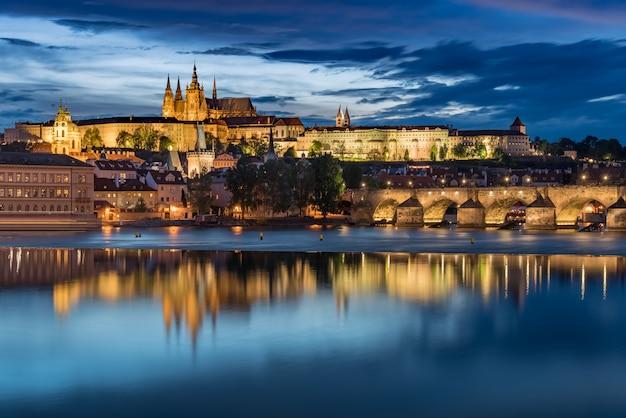 Prager burg mit blauem himmel des bewölkten sonnenuntergangs und charles bridge leuchten