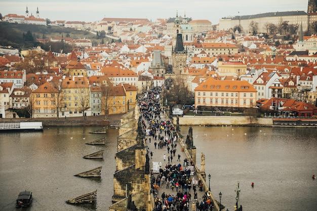 Prager panorama mit roten dächern von oben. karlsbrücke und prager burg.