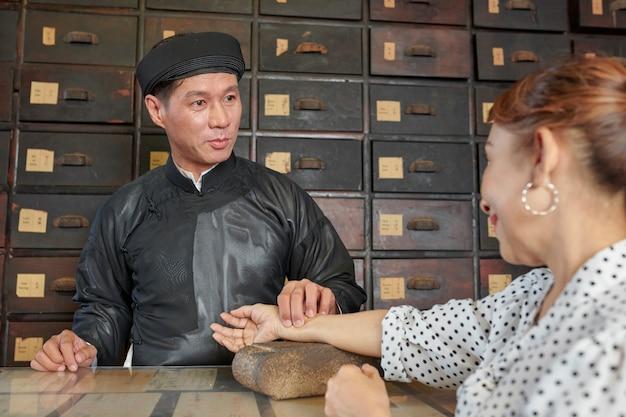 Praktiker der traditionellen medizin, der puls der reifen frau prüft