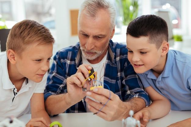 Praktische lektion. nette kluge kinder sitzen um ihre kinder herum und beobachten seine arbeit