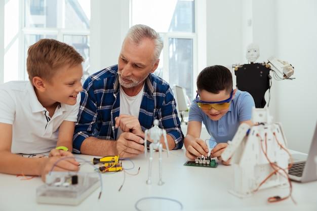 Praktisches wissen. positive freudige kinder sitzen um ihren lehrer herum, während sie gemeinsam eine praktische klasse haben