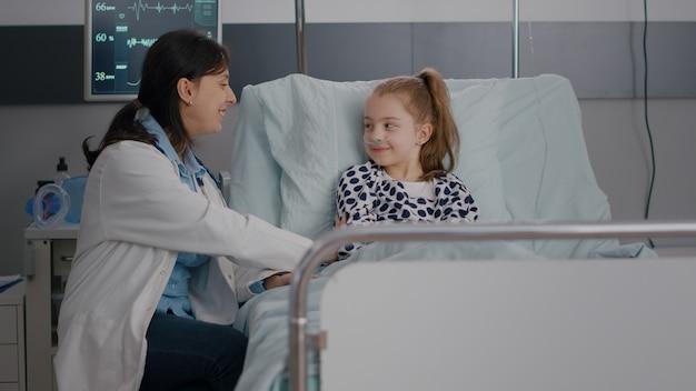 Praktizierende kinderärztin ärztin, die einem kranken kind die genesungsbehandlung erklärt, das high five gibt
