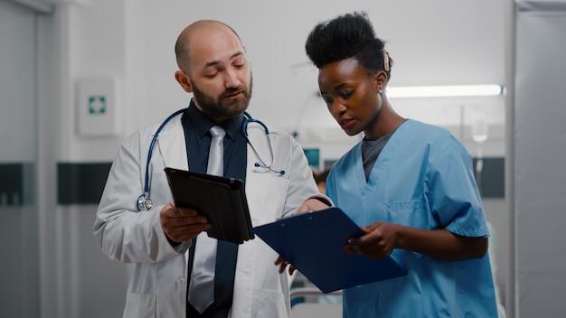 Praktizierender arzt mit afroamerikanischer assistentin, die die genesungsbehandlung analysiert