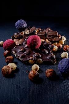 Praline der praline mit schokoladenstücken und fliegendem kakaopulver auf einem dunklen hintergrund.