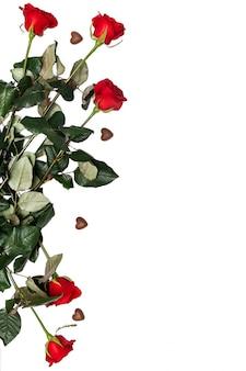 Praline und rote rosen getrennt mit copyspace. valentinstag romantisch. herzförmige süßigkeiten mit blumen flach zu legen