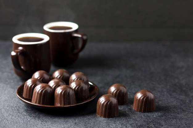 Pralinen auf einem teller und zwei tassen heißen kaffee auf schwarz