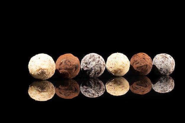 Pralinen auf einer dunklen oberfläche mit reflexion. abfüllung von nüssen und früchten. platz kopieren.