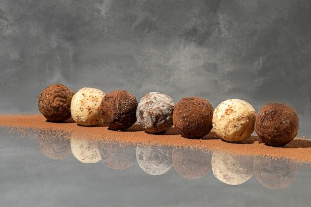 Pralinen auf einer grauen oberfläche mit reflexion. abfüllung von nüssen und früchten. platz kopieren.