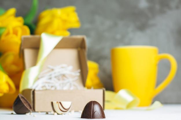Pralinen in bastelkiste, tasse und strauß gelber tulpen auf weißer holzoberfläche an grauer wand. platz kopieren