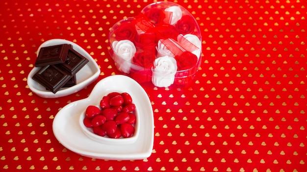 Pralinen in der herzförmigen platte, weiße und rote rosen auf rotem grund. valentinstag romantisches geschenk, süßigkeiten und romantik