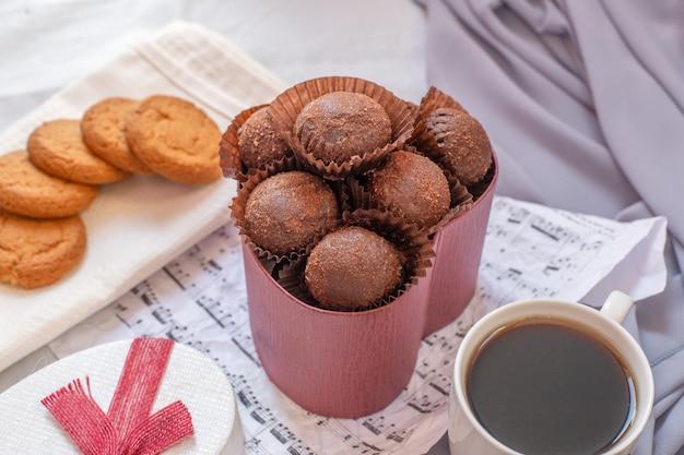 Pralinen, kekse und eine tasse kaffee.