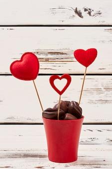 Pralinen und rote herzen. blumentopf auf hölzernem hintergrund. schokolade ist das beliebteste geschenk.