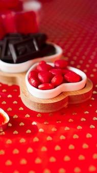 Pralinen und süßigkeiten auf herzförmigen tellern. festliche tischdekoration für verliebte. roter hintergrund. vertikales foto