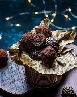 Pralinetrüffel mit schokoladenstücken und fliegendem kakaopulver auf einem dunklen hintergrund. gesunde süßigkeiten. vegane süßigkeiten. neujahrs-dessert. weihnachtsdessert. valentinstag
