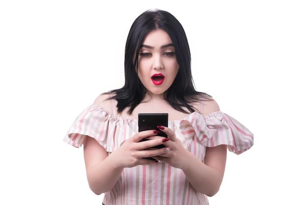 Pralle frau schaut in das telefon mit schockierter emotion, isoliert auf weißem hintergrund