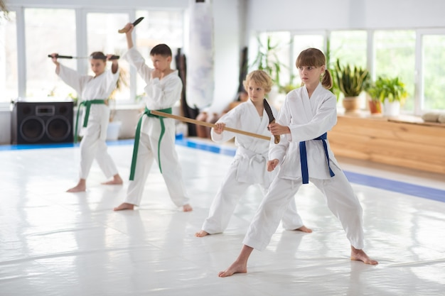 Praxis am wochenende. jungen und mädchen im weißen kimono, die am wochenende kampfkunst lernen