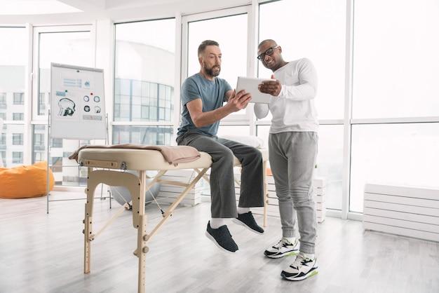 Praxis. schlauer erwachsener mann, der auf der medizinischen couch sitzt, während er mit seinem therapeuten auf den tablettbildschirm schaut