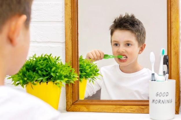 Pre-teen-kinderjunge im pyjama, der seine zähne mit einer zahnbürste putzt und morgens sein spiegelbild im badezimmer betrachtet, rückansicht.