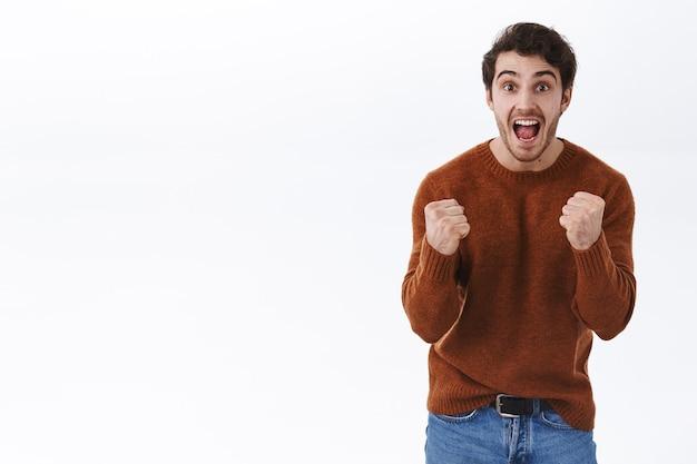 Preis, lotterie und gewinnkonzept. aufgeregt glücklicher junger mann schreit ja vor erfolg, ziel erreichen, faustpumpe