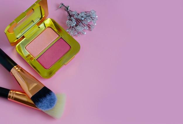 Premium make-up pinsel in kosmetiktasche, erröten palette auf einem farbigen rosa hintergrund