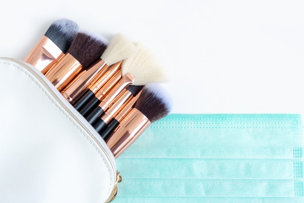 Premium make-up pinsel in weißer kosmetiktasche und schützender gesichtsmaske auf weißem hintergrund