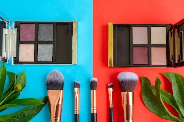 Premium make-up pinsel, palette lidschatten auf einem bunten blauen und roten hintergrund, kreative kosmetik flach legen
