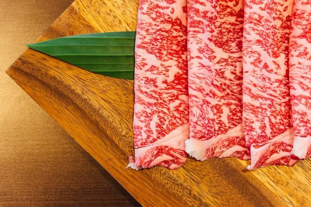 Premium rare slices wagyu a5 rindfleisch mit hochmarmorierter textur auf quadratischen holzplatten